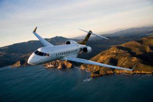 Le jet privé Bombardier Global 6000 en vol avec un couché de soleil, la mer et des montages